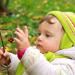 Baby girl holding ash berry in hand and looking on autumn backgr — Stock Photo #13792450