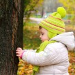 Thinking baby looking on big tree and touching on autumn yellow — Stock Photo