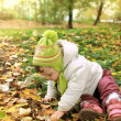 Baby girl sitting on yellow leaves and looking in sunny autumn d — Stockfoto