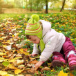 Baby girl sitting on yellow leaves and looking — Stock Photo