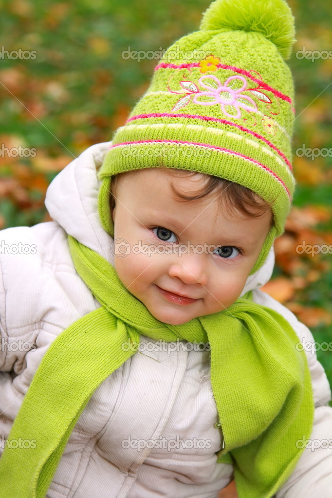 Smiling baby girl closeup portrait in hat looking in camers on outdoor bright yellow autumn background  Stock Photo #13813711