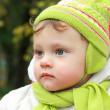 Stock Photo: Closeup portrait of serious baby looking in hat and scarf on aut