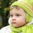 Closeup portrait of serious baby looking in hat and scarf on aut — Stock Photo