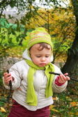 Fun baby girl looking on branches on yellow bright trees autumn — Stock Photo