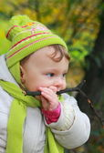 Fun baby tasting branch on yellow autumn. Closeup portrait — Stock Photo