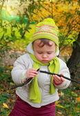 Dítě při pohledu na větvi drží v rukou venku podzimní zábava zpět — Stock fotografie