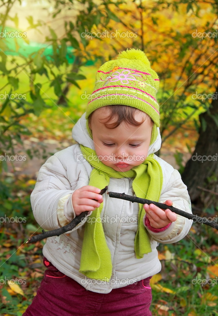 Fun baby looking on branch holding in hands in hat and scarf outdoors autumn yellow background — Stock Photo #13971810