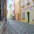 Narrow medieval street among the houses in old Prague city cente — Stock Photo #16352145