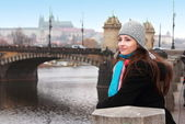 Beautiful thinking woman on Prague river old bridge background h — Stock Photo