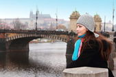 Thinking beautiful woman looking on Prague bridge autumn backgro — Stock Photo