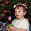 Smiling baby at fir Christmas tree holding gift with happy look — Stock fotografie