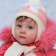 Winter baby girl in hat looking blue fun eyes in red coat. Close — Stock Photo
