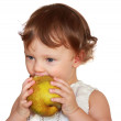 Baby eating yellow fruit pear isolated on white background — Stock Photo