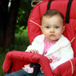 Baby sitting in stroller with fun look on summer green backgroun — Stock Photo