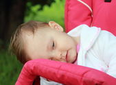 Tired baby on buggy wanting to sleep outdoor background. Closeup — Stock Photo