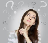 Beautiful girl with questioning thinks and question marks above — Stock Photo