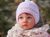Baby girl in hat and scarf outdoor spring background. Closeup po — ストック写真