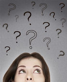 Beautiful thinking woman looking on questions marks above her he — Stock Photo