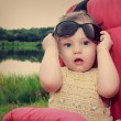 Surprising baby girl holding sunglasses outdoors summer backgrou — Stock Photo