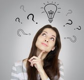 Thinking woman with question signs and light idea bulb above — Stock Photo