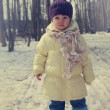 Baby girl in hat looking on winter snow and trees background — Stock Photo