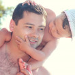 Smiling father holding baby girl on shoulders on summer holidays — Stock Photo