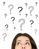 Woman looking up on question marks above head isolated on white — Stock Photo