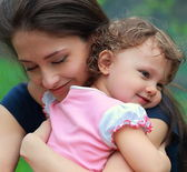 Happy mother and daughter cuddling outdoor green background — Stock Photo