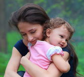 Smiling happy mother and cute kid girl cuddling outdoor summer b — Stock Photo