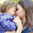 Loving mother holding small happy girl and smiling. Closeup port — Stock Photo