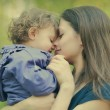 Stock Photo: Happy loving mother and baby girl embracing outdoor summer backg