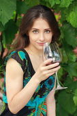 Beautiful woman drinking red wine in park on nature green backgr — Stock fotografie