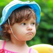 Angry baby girl looking in blue hat on summer background. Closeu — Stock Photo