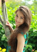 Beautiful smiling girl near the tree looking on summer backgroun — Stock Photo