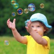 Happy child playing with bubbles on summer background. Closeup p — Stock Photo
