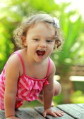 Happy girl playing on summer green background outdoor — Stock Photo