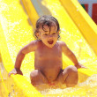 Screaming shocked baby girl riding down on water slide in aqua p — Stock Photo