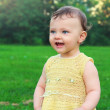 Fun baby girl looking happy on green grass summer background. Po — Stock Photo