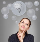 Thinking smiling woman looking up on many bubbles with idea bulb — Stock Photo