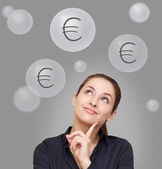 Thinking happy woman looking up on euro signs above on grey back — Stock Photo