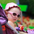 Fashion baby girl sitting in pram in pink sunglasses and cap in  — Stock Photo