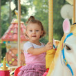 Stock Photo: Happy smiling girl riding on horse on carousel outdoors summer b