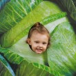 Fun smiling child girl looking from big green cabbage — Stock Photo #29791653