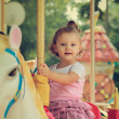 Stock Photo: Happy smiling girl riding on carousel on summer background. Vint