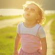 Child girl in sunglasses looking up in yellow sunlight on summer — Stock Photo #29791913