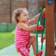Small girl climbing up on children activity ladder outdoors summ — Stock Photo #29850341