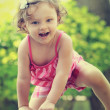 Small happy child girl climbing and looking in camera on summer. — Stock Photo #29890015