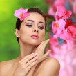 Beautiful woman with pink flowers. Beauty model perfect skin fac — Stock Photo