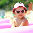 Cute girl in pink sunglasses and hat sitting in kid swimming poo — Stock Photo