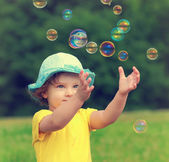 Happy baby girl playing with bubbles the hands on summer green b — Stock Photo